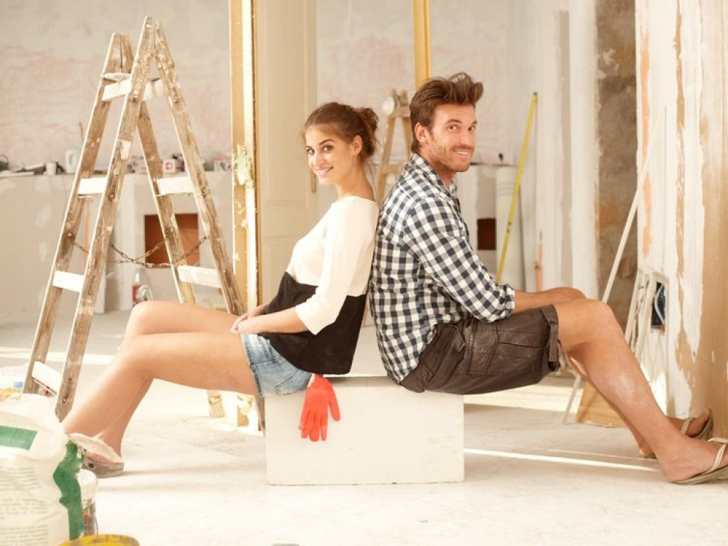 17423429 - happy young couple sitting happy in home under construction   65533;